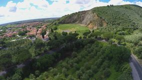 Vogelperspektive der kurvenreicher Straße zum schönen italienischen Dorf, das nahe grasartigem Hügel liegt stock video
