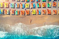 Vogelperspektive der Lügenfrau auf dem Strand mit bunten Wagenaufenthaltsräumen stockfotos