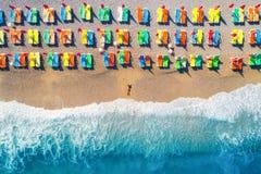 Vogelperspektive der Lügenfrau auf dem Strand mit bunten Wagenaufenthaltsräumen stockfotografie