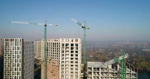 Vogelperspektive der Landschaft in der Stadt mit im Bau Gebäuden und industriellen Kränen Ziegelsteine, die draußen legen stock footage