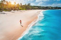 Vogelperspektive der laufenden jungen Frau auf dem sandigen Strand stockfoto