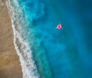 Vogelperspektive der Schwimmens der jungen Frau auf dem rosa Schwimmenring Lizenzfreies Stockfoto