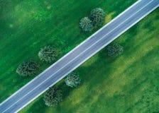 Vogelperspektive der Straße durch schönes grünes Feld Lizenzfreie Stockfotos