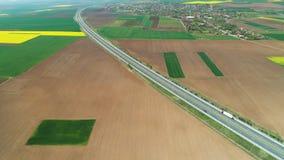 Vogelperspektive des Ackerlands, der Rapssamen- und Weizenfelder und der Landstra?enstra?e in der Landschaft stock footage