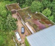 Vogelperspektive des altmodischen überwucherten Dachs einer ehemaligen Sporthalle Lizenzfreies Stockbild