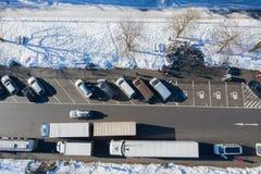 Vogelperspektive des AutomobilParkplatzes mit Autos nahe Landstraße im Winter mit Schnee stockbilder