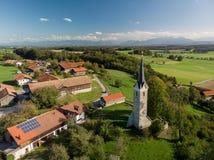 Vogelperspektive des bayerischen Dorfs nah an den Alpenbergen stockbild