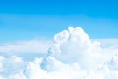 Vogelperspektive des blauen Himmels und Wolkenspitzeansicht vom Flugzeugfenster, Stockfoto