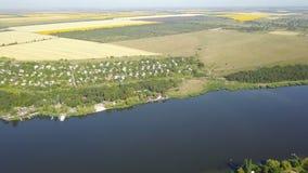 Vogelperspektive des Dorfs nahe Fluss, Brummen schoss von der ländlichen Sommerlandschaft stock video