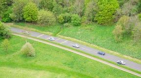 Vogelperspektive des Fahrens mit fünf Autos in eine Landschaftsstraße stockbilder