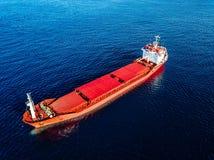 Vogelperspektive des Frachtschiffs im blauen Meer Ansicht von oben des roten Leercontainerschiffs im Meer stockfotografie