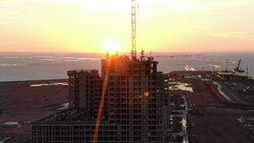 Vogelperspektive des Gebäudes im Bau bei Sonnenuntergang, Effekt des Transportwagenlauten summens stock footage