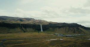 Vogelperspektive des Gebirgstales und des Seljalandsfoss-Wasserfalls Hubschrauber, der über den berühmten touristischen Platz in  stock video