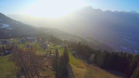 Vogelperspektive des gemütlichen Dorfs auf grünem Gebirgshügel, magische Stunde in den österreichischen Alpen stock video