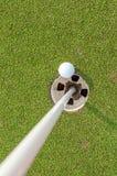 Vogelperspektive des Golfballs nahe Stift und Loch auf grünem Gras von gol Lizenzfreies Stockbild