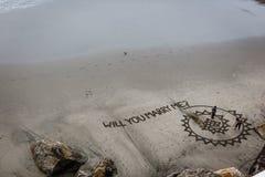Vogelperspektive des Heiratantrages, der in den Sand auf den Strand unter die Klippe geschrieben wird Lizenzfreies Stockfoto