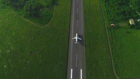 Vogelperspektive des Jagens des Flugzeuges, das das Durchgehen mitten in grünem Rasen entfernt 4K stock footage