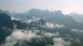 Vogelperspektive des Kalksteins schaukelt in den Nebel, der mit dem üppigen tropischen Grün bedeckt wird Draufsicht von Bergen in stock video footage