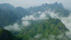 Vogelperspektive des Kalksteins schaukelt in den Nebel, der mit dem üppigen tropischen Grün bedeckt wird Draufsicht von Bergen in stock footage