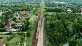Vogelperspektive des Land-Bahnhofs im Sommer Häuser, Autos, Zug auf Eisenbahn stock footage