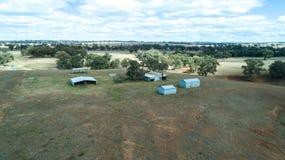 Vogelperspektive des landwirtschaftlichen Bauernhofhallen- und -heuspeichers bellt auf Ackerland mit Eukalyptuseukalypten, New So Lizenzfreies Stockbild