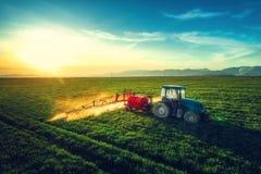 Vogelperspektive des Landwirtschaftstraktors pflügend und auf Feld sprühend Lizenzfreies Stockfoto