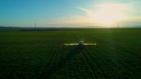 Vogelperspektive des Landwirtschaftstraktors pflügend und auf grünes Feld sprühend stock footage