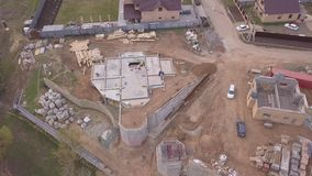 Vogelperspektive des neuen modernen Häuschens nahe der Baustelle, den Baumaterialien und den Arbeitskräften, die Beton für gießen stock footage