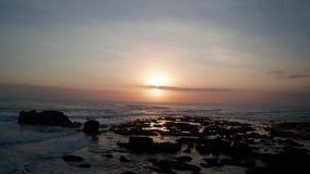Vogelperspektive des schönen Sonnenuntergangs über Meer und schwarzem Sandstrand stock video footage