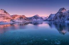 Vogelperspektive des Schnees bedeckte Berge und Meer bei buntem Sonnenuntergang stockfotografie