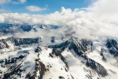 Vogelperspektive des Schnees umfasste Gebirgszug mit Wolken Lizenzfreie Stockfotografie