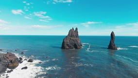 Vogelperspektive des schwarzen vulkanischen Strandes und der Felsen auf dem Meer in Island stock footage