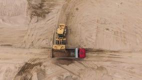Vogelperspektive des strömenden Sandes der Planierraupe in LKW Stockbilder
