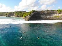 Vogelperspektive des Surfers die Wellen auf ihrem Brett genießend, die Wellen als nächstes wartend die Klippe stockfotos