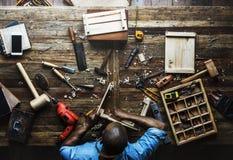Vogelperspektive des Tischlermannes arbeitend mit Werkzeugausrüstungssatz stockfoto