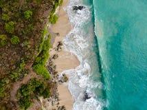 Vogelperspektive des tropischen Sandstrandes mit Felsen und grüner Klippe stockbilder