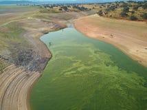 Vogelperspektive des Valdecañas-Reservoirs, mit grünem Wasser von den Algen und natürliche Linien des Abfalls des Wassers frech stockbilder