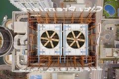 Vogelperspektive des Ventilators zwei, der auf das Dach des Wolkenkratzers spinnt Auf der linken Seite des Gebäudes können Sie de Stockbilder