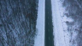 Vogelperspektive des Verkehrs auf der Straße, die durch den Winterwald im Unwetter überschreitet stock footage