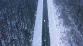 Vogelperspektive des Verkehrs auf der Straße, die durch den Winterwald im Winter überschreitet stock video footage