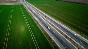 Vogelperspektive des Verkehrs auf zweispuriger Stra?e durch Landschaft und bebaute Felder stockbilder