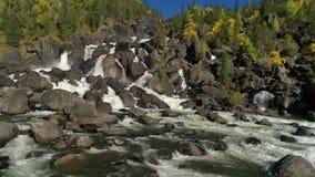 Vogelperspektive des Wasserfalls, fliegend über Herbstwald, Wasserfall mit großen Steinen stock footage