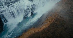 Vogelperspektive des Wasserfalls Gullfoss in der Spalte Hubschrauber, der über das Tal und den turbulenten Fluss in Island fliegt stock footage