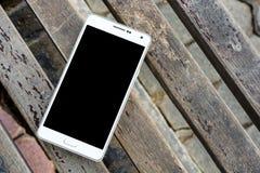 Vogelperspektive des weißen intelligenten Telefons mit Schwarzem lokalisiert auf hölzernem sur Stockbilder