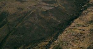 Vogelperspektive des wilden Flusses fließt in das Tal Hubschrauber, der über die grünen Felder fliegt Lavaberge in Island stock video footage