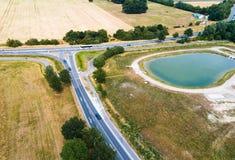 Vogelperspektive des Zusammenströmens von zwei Landstraßen nahe bei einer Neuentwicklung mit einem Regenzurückhaltenbecken lizenzfreie stockbilder
