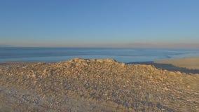 Vogelperspektive einer felsigen Halbinsel mit einem großen See, einem Meer oder einem Ozean, die heraus zu den entfernten Bergen  stock video footage