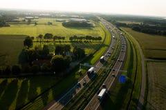 Vogelperspektive einer Landstraße mit grünen Feldern stockfotos