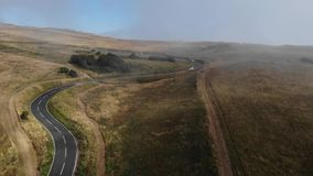Vogelperspektive einer leeren Straße zwischen Hügeln Straße mit vielen Wolken und Nebel stock video