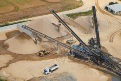 Vogelperspektive einer Sandfabrik mit Sandhaufen und Schwermaschinen stockbild